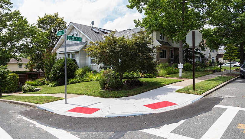 Two newly built pedestrian ramps on a corner in front of a house