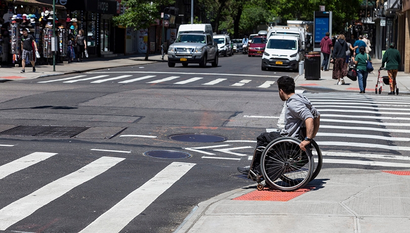 Man in a wheelchair going down a pedestrian ramp