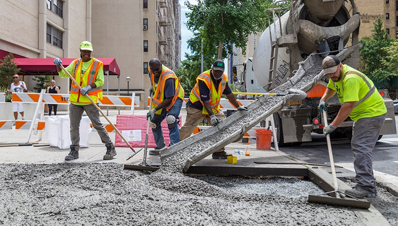 Construction workers laying down cement for a new sidewalk corner